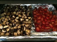 """Mushrooms and tomatoes in their foil """"tray"""" ready for roasting."""